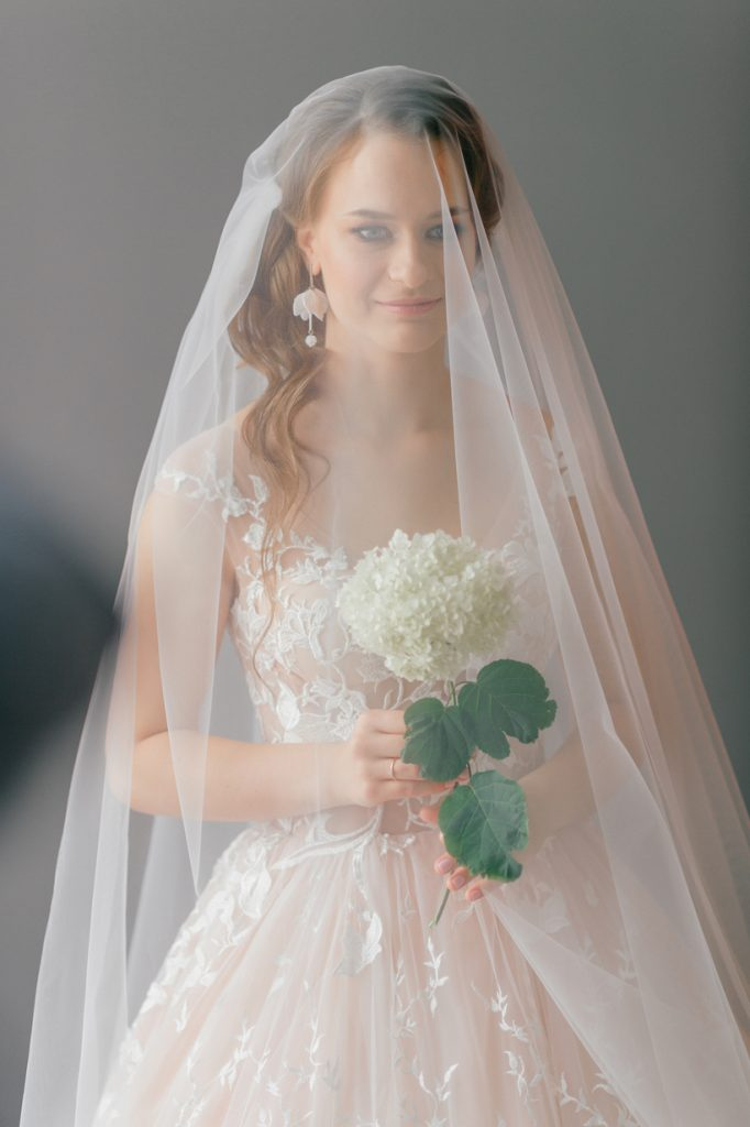 Velo de novia largo modelado por mujer blanca